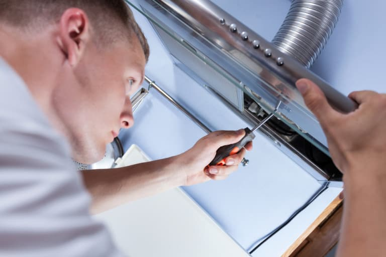 Repairman mending a kitchen extractor